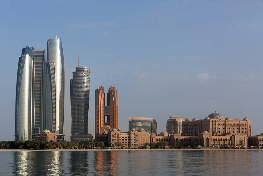 Emirates Palace Hotel and the Etihad Towers standing prominently on the Abu Dhabi skyline.