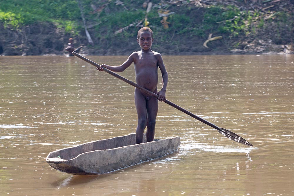 A young boy paddling in a dugout canoe in the Karawari river.