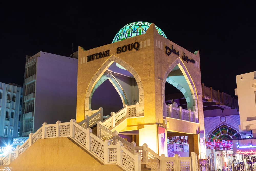 Muttrah souq entrance illuminated at night.