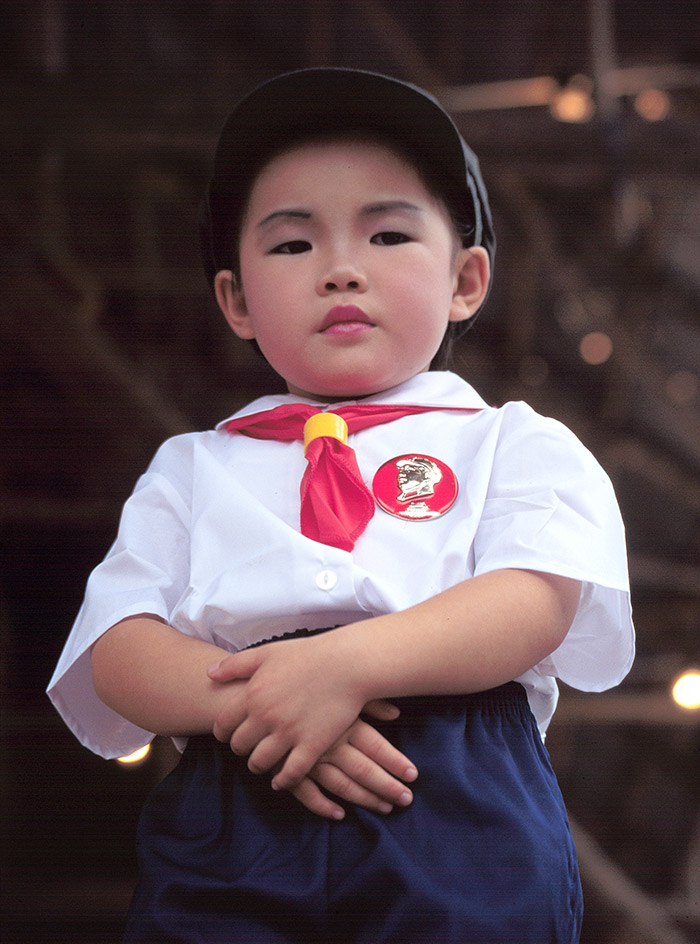 A young boy dressed as Chairman Mao.