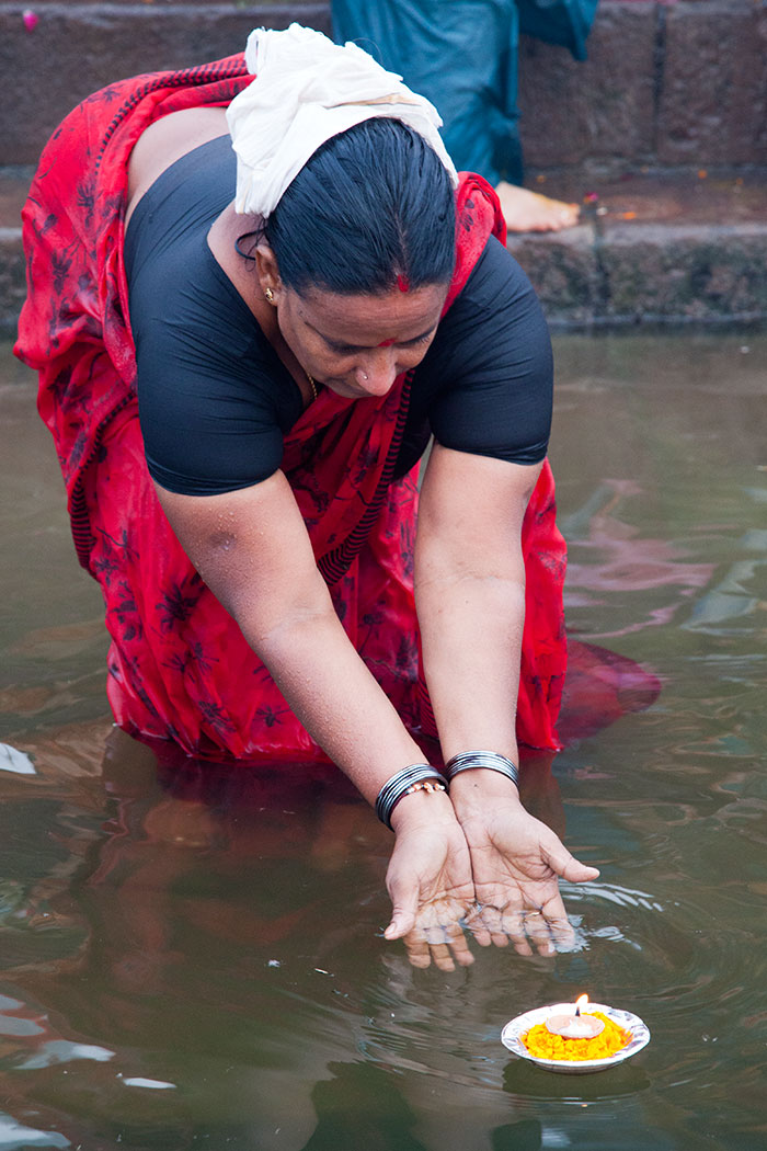 A woman launches an offering into the Ganges.