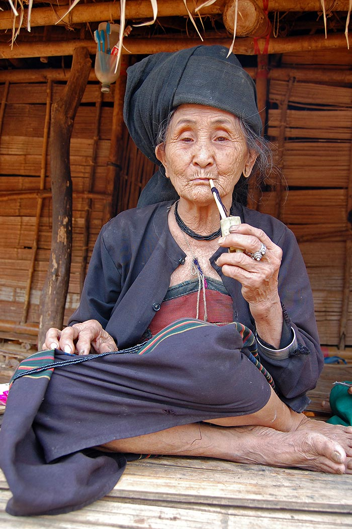A pipe smoking Akhu woman.