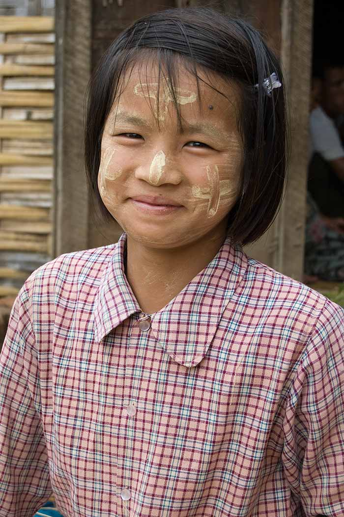 A young woman harvesting rice near Inle Lake.