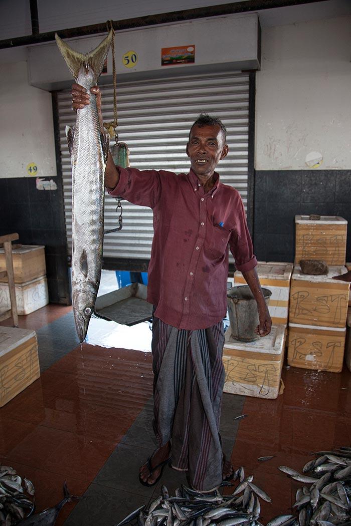 A fish vendor holds up a barracuda for me..