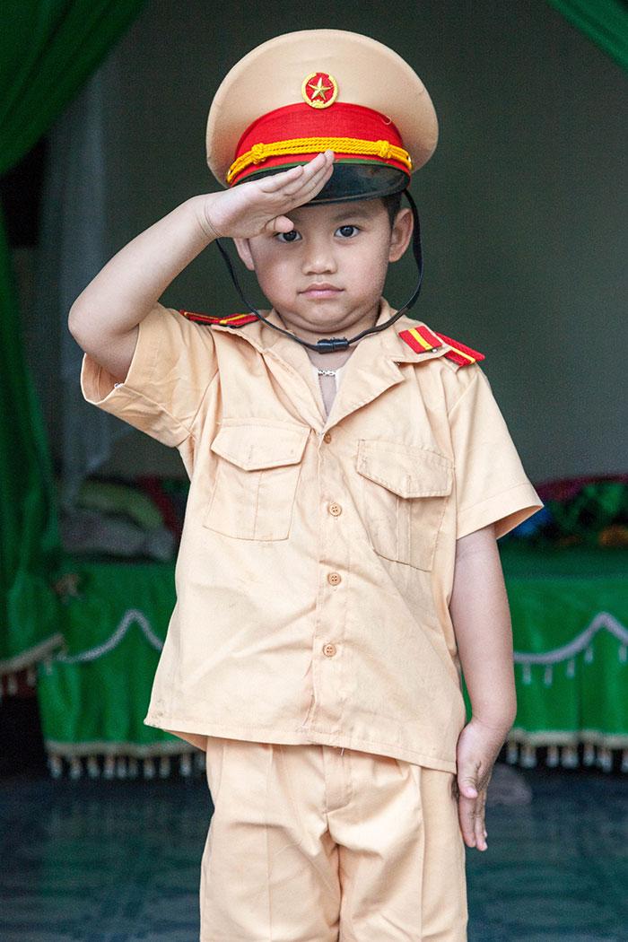 A Vietnamese boy dressed in a police uniform