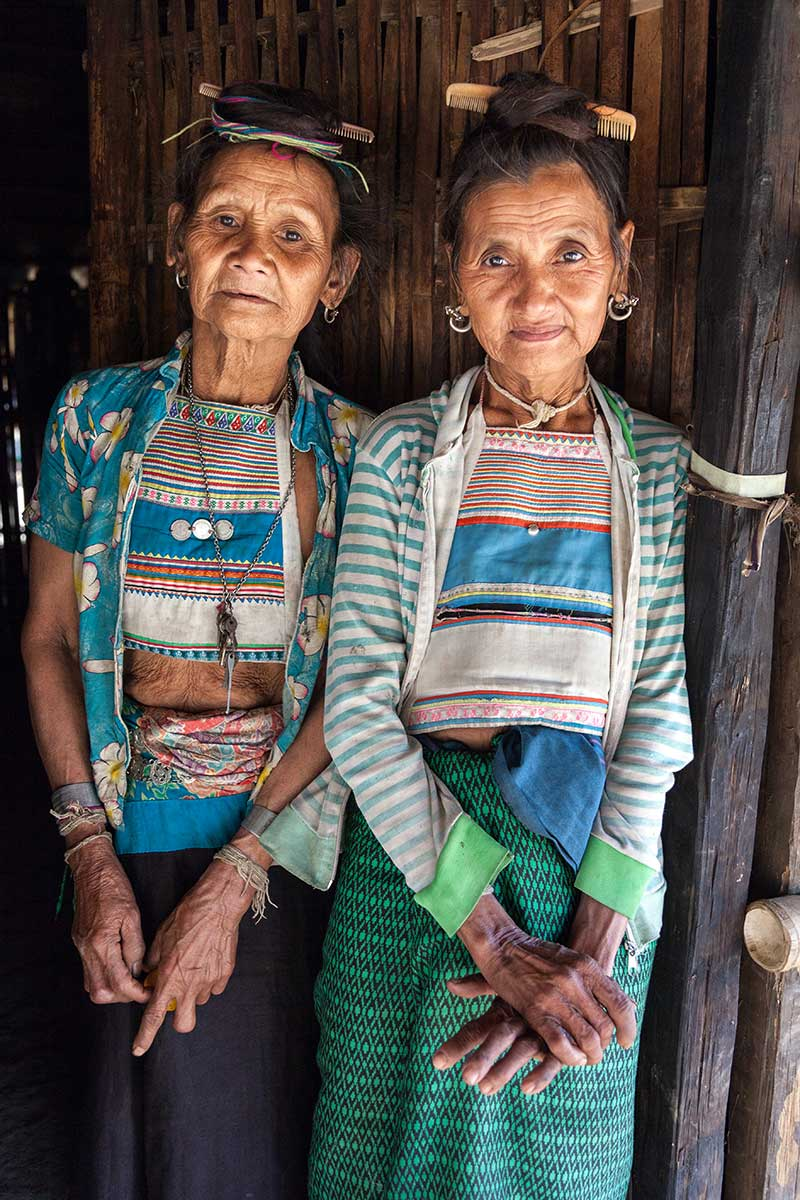 Two Khoui minority women, with distinctive combs in their hair.