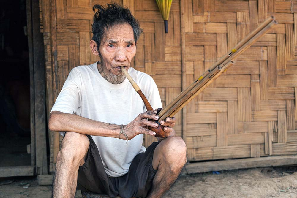 """A Khou man, high on opium, playing a traditional instrument called a """"Khen""""."""