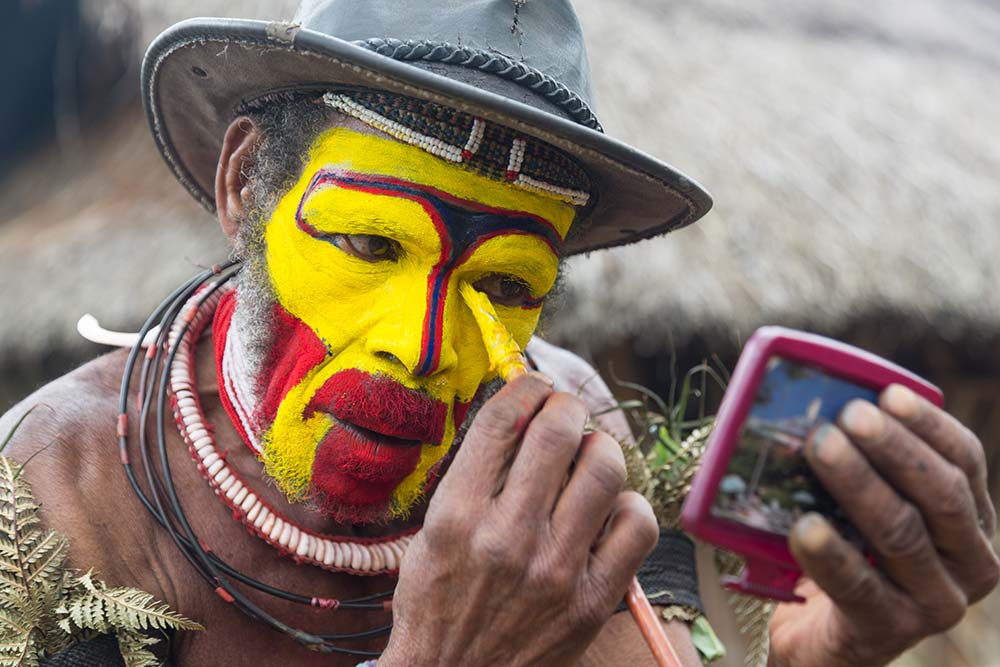 A Huli man paints his face in preparation for a Sing Sing.