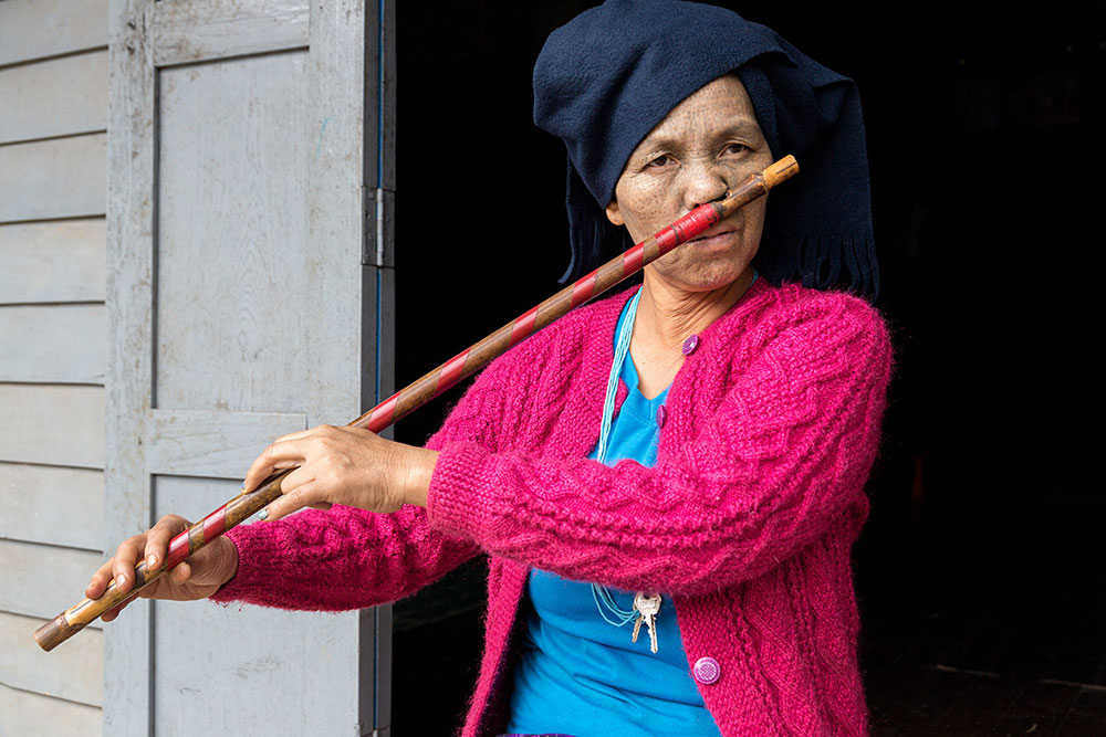 A Dai Chin woman playing traditional nose flute.