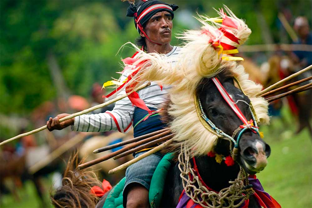 A spear-wielding rider in Sumba's Pasola Harvest Festival